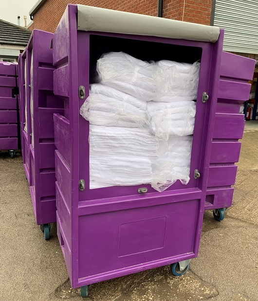 Plastic laundry roll cages help protect linen out-of-doors